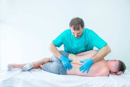 Male neurologist doctor diagnoses the lumbar spine of male patient in medical clinic. Neurological physical examination. Osteopathy, chiropractic, physiotherapy.