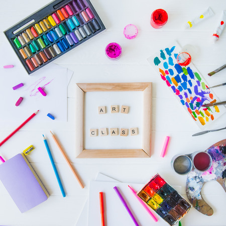 Top view creative art class concept. Canvas in frame with lettering inside and many colorful paintiing materials on white wooden background. Drawing lesson for children and adults. Flat lay. Square.