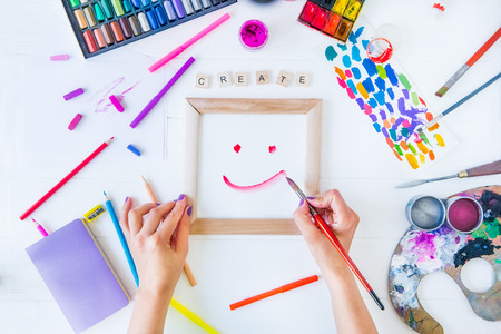 Top view Female Hands drawing smile on canvas with Create word lettering and many colorful paintiing materials on white background. Add colors to your life, be cheerful motivated inspired Concept
