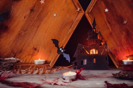 Halloween holiday concept . Lighting paper silhouettes of old castle, ghosts, witch, bats, candles on the wooden background with autumn dry leaves. Spooky holiday card. Copy space 写真素材