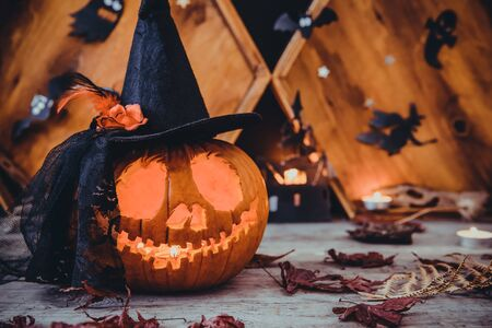 Close up carved pumpkin in witch hat with paper silhouettes of bats, castle, ghosts on wooden background. Head jack lantern with scary evil faces. Spooky holiday symbol, concept. Copy space