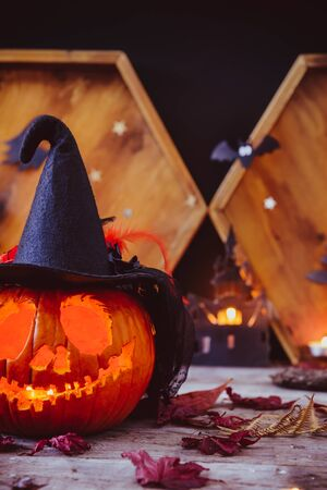 Close up carved pumpkin in witch hat with paper silhouettes of bats, castle, ghosts on wooden background. Head jack lantern with scary evil faces. Spooky holiday symbol, concept. Vertical. Copy space