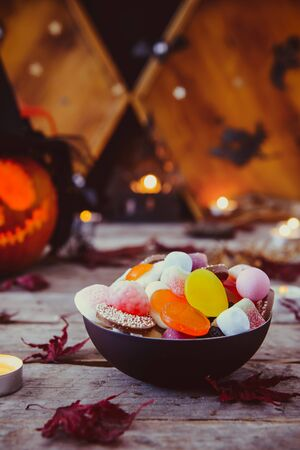 Close up bowl with candies and carved pumpkin in witch hat with paper silhouettes of bats, castle, ghosts on wooden background. Spooky holiday symbols. Trick or treat concept. Copy space