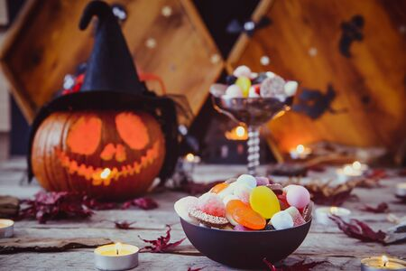 Close up bowl with sweets, candies and carved pumpkin in witch hat with paper silhouettes of bats, castle, ghosts on wooden background. Spooky holiday symbols. Trick or treat concept. Copy space