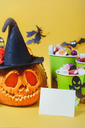 Carved pumpkin in hat, blank card and cups with sweets, candies decorated with silhouettes of bats, witch, ghosts on yellow background. Spooky holiday symbols. Trick or treat. Vertical. Copy space