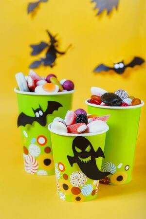 Halloween trick or treat sweets. Paper cups with colourful candies inside and paper silhouettes of bats, ghosts and witch on bright yellow background.