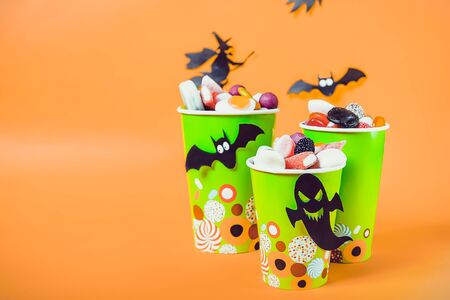 Halloween trick or treat sweets. Paper cups with colourful candies inside and paper silhouettes of bats, ghosts and witch on bright orange background.