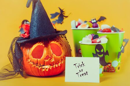 Carved pumpkin in hat, Trick or treat card and cups with sweets, candies decorated with silhouettes of bats, witch, ghosts on yellow background.