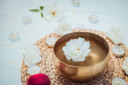 Tibetan singing bowl with floating in water rose inside. Special sticks, burning candles, flowers petals on the white wooden background. Meditation and Relax. Exotic massage. Copy space