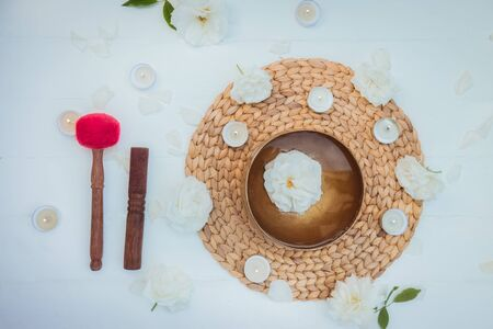 Top view Tibetan singing bowl with floating in water rose inside. Special sticks, burning candles, flowers petals on the white wooden background. Meditation and Relax. Exotic massage. Copy space 写真素材