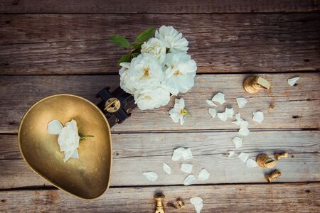 Top view antique vintage measuring scale weights with fresh white tea rose flowers on the rustic wooden background. Nature ingredients. Pure and simpiity concept. Flat lay. Selective focus. Copy space