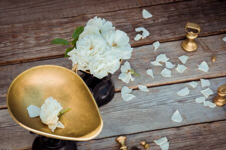 Top view antique vintage measuring scale weights with fresh white tea rose flowers on the rustic wooden background.