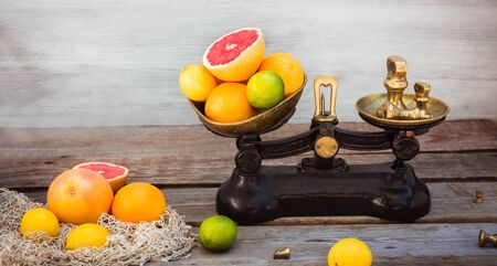 Fresh citrus fruits on the one scale plan of vintage weights and and few oranges, lemons, grapefruit, lime on the rustic wooden table. Detox diet. Harvest concept. Farmer market. Wide banner. Copy spa