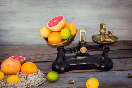 Fresh citrus fruits in vintage scale and several oranges, lemons, grapefruit, lime on the old rustic wooden table with a few weights.