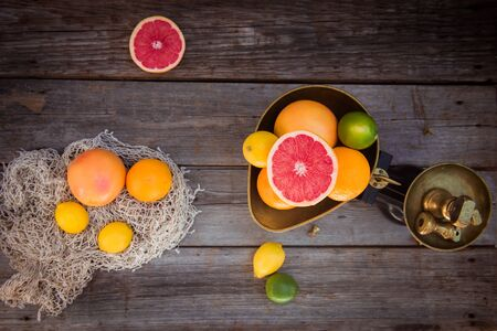Top view Fresh citrus fruits in vintage scale and several oranges, lemons, grapefruit, lime on the old rustic wooden table with a few weights. Detox diet. Harvest concept. Farmer market. Copy space