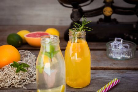 Two bottles with homemade lemonade and orange fresh juice with mint and ice on the rustic wooden background