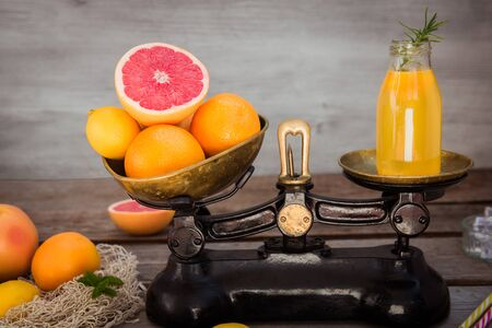 Fresh citrus fruits on the one scale plan of vintage weights and homemade juice on the other. Equivalent healthy value.