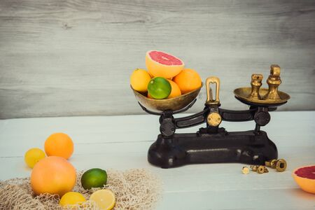 Fresh citrus fruits on the one scale plan of vintage weights and several oranges, lemons, grapefruit, lime on the white wooden table.