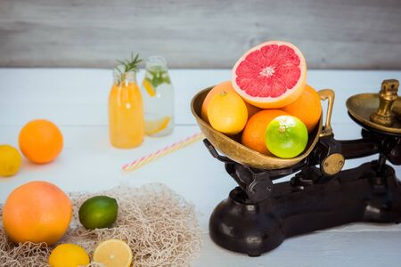 Fresh citrus fruits in vintage scale and several oranges, lemons, grapefruit, lime and homemade drinks on the white wooden table with a few weights. Healthy detox diet. Harvest concept. Copy space