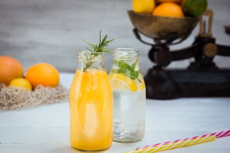 Two bottles with homemade lemonade and orange fresh juice with mint and ice on the white wooden background 写真素材