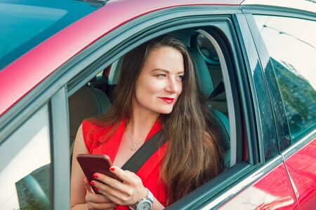 Young caucasian woman driver in red suit holding her cell smart phone and looking away while sitting behind the wheel red car. Selective focus, copy space