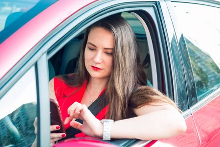 Young business woman driver in red suit holding and looking on her cell smart phone while sitting behind the wheel red car. Selective focus, copy space