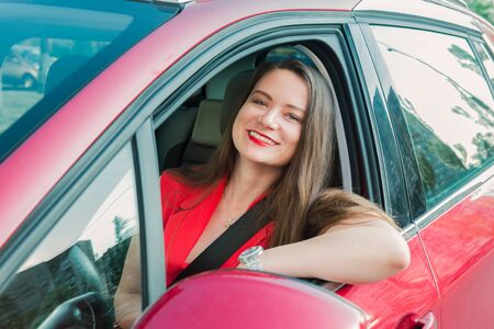 Happy smiling woman in a car. Driving. Portrait of young caucasian business lady in red clothes looking at camera while sitting behind the wheel red car. Selective focus, copy space Stockfoto