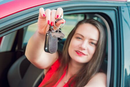 Focused car shaped keychain with keys on the background of happy successful woman sitting in her new car. Outdoors view. Selective focus, copy space Banque d'images