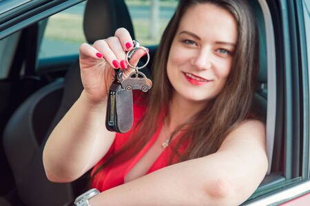 Focused car shaped keychain with keys on the background of happy successful woman sitting in her new car. Outdoors view. Selective focus, copy space Stok Fotoğraf