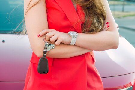 Recadrée, sans visage, jeune femme d'affaires caucasienne réussie, vêtue de vêtements rouges, tenant un porte-clés en forme de voiture avec des clés debout sur le fond de sa voiture rouge. Fermer. Mise au point sélective, espace de copie