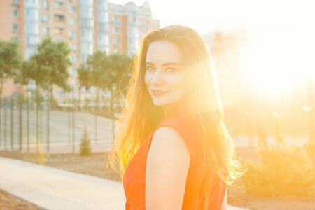 Back light portrait of a happy smiling young woman, business lady in red suit at sunset in a park with a warm yellow light and urban background. Selective focus, copy space