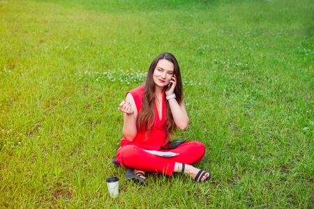Young business woman plus size in red suit speaking her phone and seating on the background of green lawn with notebook and pen in her hand. ,orking Outdoor break ,Business Concept. Copy space