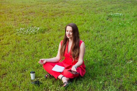 Young businesswoman in red suit sitting in lotus position on green grass in park and holding her smart phone. Meditation for lfe. Calm, relaxed lifestyle. Selective focus. Copy space