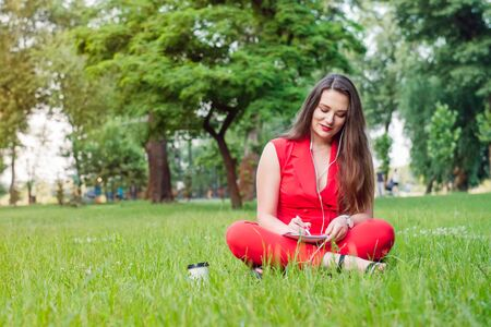 Portrait of young smiling business woman in red suit in earphones, doing online learning cources and writing in notebook while sitting on the green grass lawn in park. Self-development. Copy space