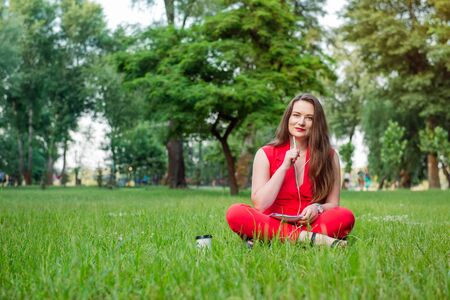 Portrait of young smiling business woman in red suit in earphones listening to music, doing online learning cources and writing in notebook while sitting on the green grass lawn in park. Copy space
