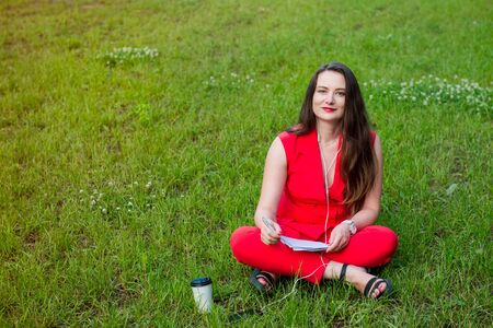 Portrait of young smiling business woman in red suit in earphones listening to music, doing online learning cources and writing in notebook while sitting on the green grass lawn in park. Copy space 스톡 콘텐츠 - 132062055