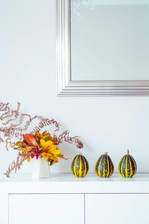 Three decorative striped pumpkins and vase with bouquet of falling leaves and fern on a white chest, table on a background of white wall with mirror. Autumn natural home interior decor. Vertical card Banco de Imagens