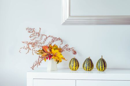 Three decorative striped pumpkins and vase with bouquet of falling leaves and fern on a white chest, table on a background of white wall with mirror. Autumn natural home interior decor. Copy space