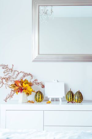 Empty blank for text on stand, decorative striped pumpkins, vase with bouquet of falling leaves and fern on a white chest, table on a background of wall with mirror. Autumn natural home interior decor.