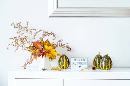 Box with text HELLO AUTUMN, decorative striped pumpkins and vase with bouquet of falling leaves and fern on a white chest, table on a background of wall with mirrow. Autumn natural home interior decor.