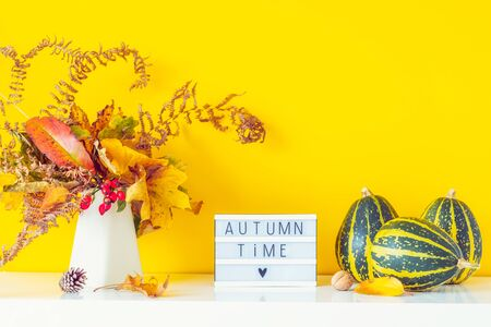 Box with text AUTUMN TIME, decorative striped pumpkins, vase with bouquet of falling leaves and fern on bright yellow wall background. Autumn natural home interior decor. Eco, simple style. Copy space.