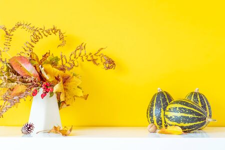Composition of decorative striped pumpkins, vase with bouquet of falling leaves and fern on a white table on yellow wall background. Autumn natural home interior decor. Eco, simple style. Copy space Banco de Imagens