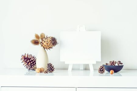 Composition of dried flowers and thorns in light vase, pine cones and empty blank canvas on a stand on white wall background. Eco, natural home interior decor. Simple style. Minimalism. Copy space Banco de Imagens