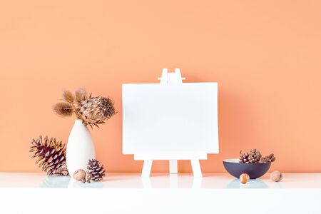 Composition of dried flowers and thorns in light vase, pine cones and empty blank canvas on a stand on salmon color background. Eco, natural home interior decor. Simple style. Minimalism. Copy space