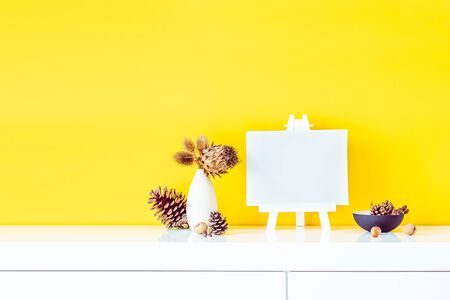 Composition of dried flowers and thorns in light vase, pine cones and empty blank canvas on a stand on yellow wall background. Eco, natural home interior decor. Simple style. Minimalism. Copy space Banco de Imagens
