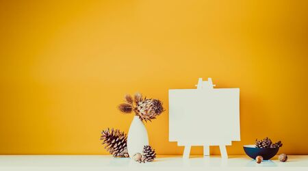 Composition of dried flowers, thorns in light vase, pine cones and blank canvas on a stand on ocher color wall background. Simple, natural home interior decor. Minimalism. Wide banner. Copy space
