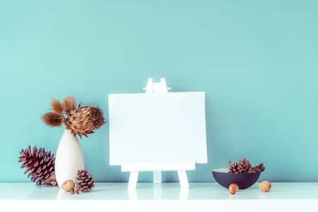 Composition of dried flowers and thorns in light vase, pine cones and empty blank canvas on a stand on turquoise wall background. Eco, natural home interior decor. Simple style. Minimalism. Copy space.