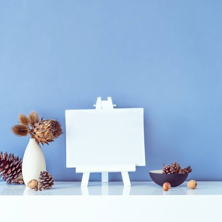 Composition of dried flowers and thorns in vase, pine cones and empty blank canvas on stand on blue wall background. Eco, natural home interior decor. Simple style. Minimalism. Square card. Copy space.