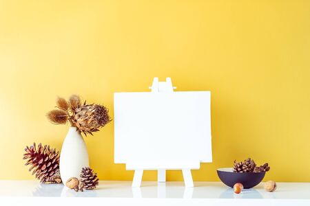 Composition of dried flowers and thorns in light vase, pine cones and empty blank canvas on a stand on golden wall background. Eco, natural home interior decor. Simple style. Minimalism. Copy space Banco de Imagens