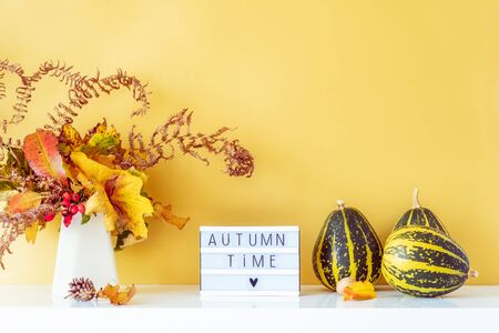 Box with text AUTUMN TIME, decorative striped pumpkins, vase with bouquet of falling leaves and fern on golden wall background. Autumn natural home interior decor. Eco, simple style. Copy space Banco de Imagens